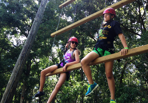 Two teenagers navigate ropes course at social skills day camp