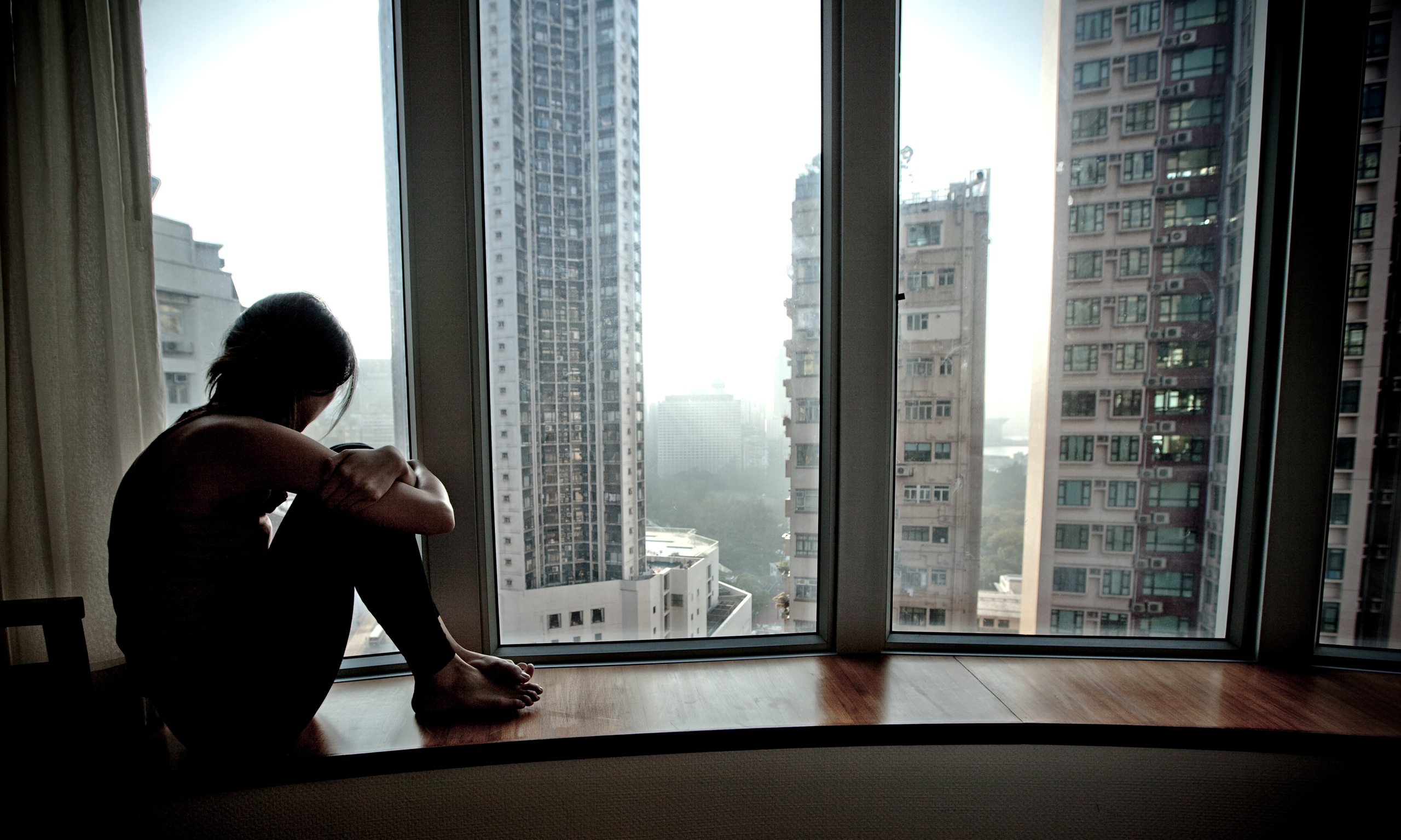 A lonely girl looking out of a high-rise flat. - Total ...