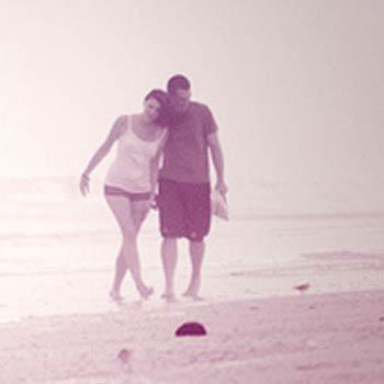 An embracing couple walk along the beach