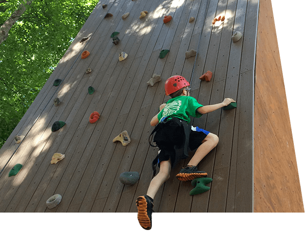 Youth scales rock wall on the ropes course at our adventure based ADHD ASD social skills camp in Orlando, Florida