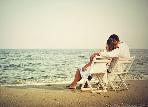 Couple sitting peacefully on chairs at beach watching the water